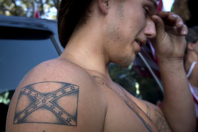 "Dennis Wiles, 20, from Tampa with a Confederate flag tattoo on his arm, listens to instructions for a ""Ride for Pride"" impromptu event to show support for the Confederate flag in Brandon, Hillsborough County, June 26, 2015. (Photo by Carlo Allegri/Reuters)"