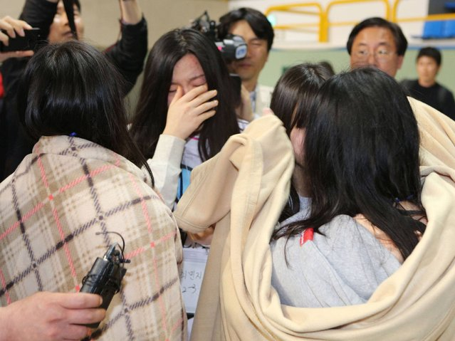 People wrapped in blankets react after the rescue. (Photo by Getty Images/Yonhap)