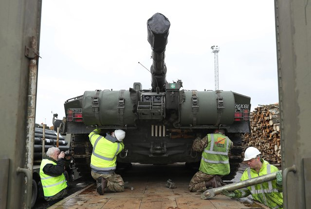 A crew secures a British Army Challenger 2 tank of the 5th Battalion The Rifles to a truck trailer after the tank and other heavy vehicles arrived by ship on March 22, 2017 at Paldiski, Estonia. British heavy tanks, light tanks, mobile artillery and other equipment unloaded at Paldiski today as part of a deployment by approximately 800 British combat troops taking part in the multinational NATO Enhanced Forward Presence battalion. NATO member states including Great Britian, France, Germany, the U.S. and Denmark are supplementing the defensive capabilities of Estonia, Latvia, Lithuania and Poland in an effort to deter Russia from attempting any military intervention in the region. (Photo by Sean Gallup/Getty Images)
