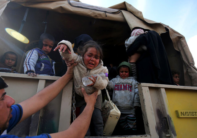 Displaced Iraqis from Mosul arrive at the Hamam al-Alil camp on March 20, 2017, during the government forces ongoing offensive to retake the western parts of the city from Islamic State (IS) group fighters. (Photo by Ahmad Al-Rubaye/AFP Photo)