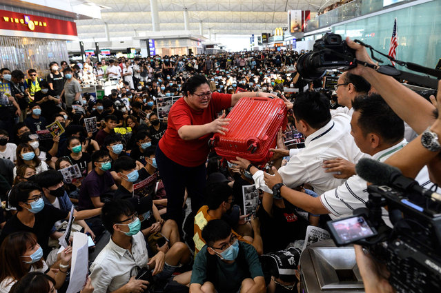 A tourist (C) gives her luggage to security guards as she tries to enter the departures gate during another demonstration by pro-democracy protesters at Hong Kong's international airport on August 13, 2019. Protesters blocked passengers at departure halls of Hong Kong airport on August 13, a day after a sit-in forced authorities to cancel all flights to and from the major international hub. (Photo by Philip Fong/AFP Photo)