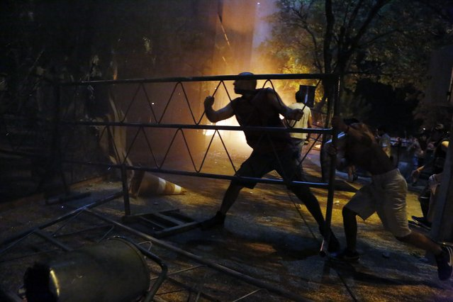 People ram a barrier into the Congress building during clashes between police and protesters opposing an approved proposed constitutional amendment that would allow the election of a president to a second term,  in Asuncion, Paraguay, Friday, March 31, 2017. Some protesters broke through police lines and entered the first floor, where they set fire to papers and furniture. Police used water cannon and fired rubber bullets to drive demonstrators away from the building while firefighters extinguished blazes inside. (Photo by Jorge Saenz/AP Photo)