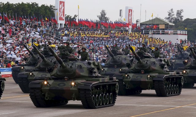 Military personnel salute as they stand on M60A3 main battle tanks displayed during the annual Han Kuang military exercise in an army base in Hsinchu, northern Taiwan, July 4, 2015. (Photo by Patrick Lin/Reuters)