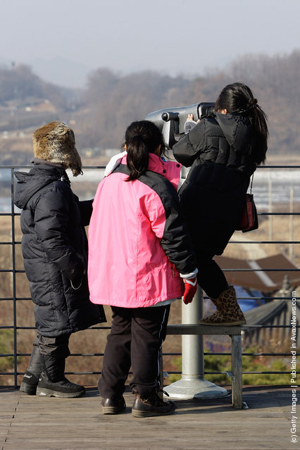 Tourists use binoculars to look over the North Korea at the Imjingak observation post