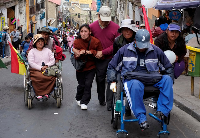 Mariel Jimenez (C) with physical disabilities, helped by his father, participates in a rally protest calling on the government to provide a monthly subsidy rather than an annual one, in La Paz, Bolivia, May 5, 2016. (Photo by David Mercado/Reuters)