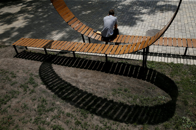 A man rests on a bench in a park in central Kiev, Ukraine July 5, 2018. (Photo by Valentyn Ogirenko/Reuters)