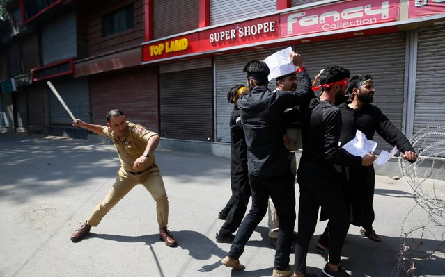 An Indian police officer beats Kashmiri Shiite Muslims as they attempt to take out a religious procession during restrictions in Srinagar, Indian controlled Kashmir, Sunday, September 8, 2019. Authorities in Indian portion of Kashmiri imposed restrictions in some parts of Srinagar fearing religious processions marking the Muslim month of Muharram would turn into anti-India protests. (Photo by Mukhtar Khan/AP Photo)