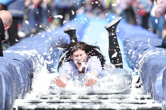 A participant takes part in the Bristol Park and Slide project, an interactive temporary  installation by artist Luke Jerram set up in Park Street in the centre of Bristol, southwest England on May 4, 2014. Over 95,000 people applied for just 360 tickets to slide on inflatable lilos down a lubricated water slide in a town centre street. (Photo by Leon Neal/AFP Photo)