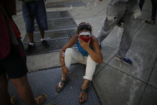 A demonstrator sits on the street overcome by tear gas during anti-government protests in Caracas, Venezuela, Wednesday, April 19, 2017. (Photo by Ariana Cubillos/AP Photo)