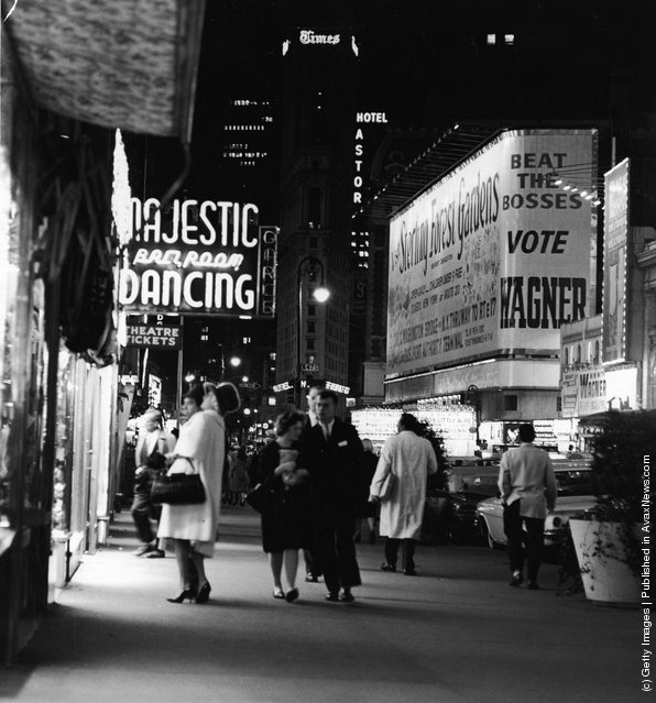 A night street scene at 47th Street near Times Square, showing night club and theater signs, New York City, New York, circa 1958