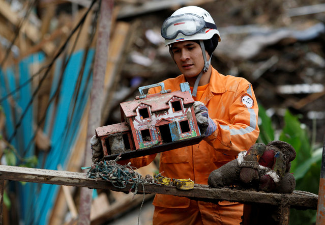 Rescue member finds a toy house in a destroyed area after mudslides caused by heavy rains leading several rivers to overflow, pushing sediment and rocks into buildings and roads, in Manizales, Colombia April 20, 2017. (Photo by Santiago Osorio/Reuters)