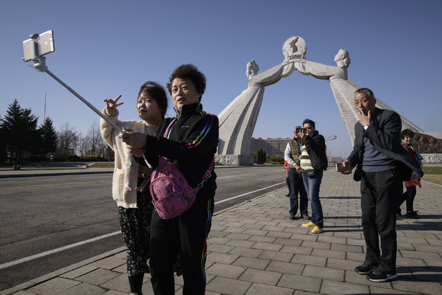 In a photo taken on April 14, 2019 tourists from China pose for photos before the Three Charters monument in Pyongyang. Ordinary Chinese pay travel companies around 2,500 yuan (360 US dollars) for a standard three-day trip to North Korea, arriving overland by train in Pyongyang to tour the capital's highlights, from the Arch of Triumph to Kim Il Sung Square. (Photo by Ed Jones/AFP Photo)