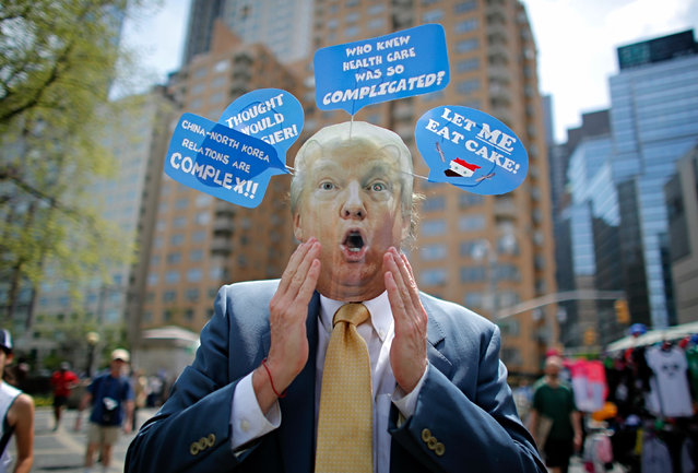 """A man wears a mask with the face of US President Donald Trump, as he takes part in the """"100 Days of Failure"""" Protest to mark the first 100 days of the Trump administration on April 29, 2017 in New York. (Photo by Kena Betancur/AFP Photo)"""