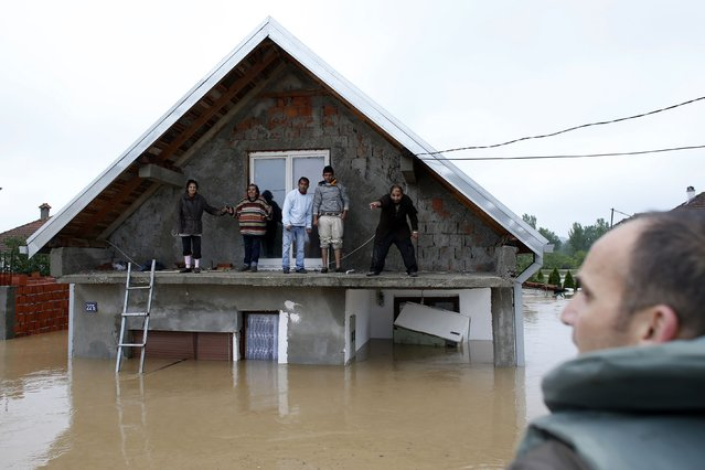 People stand on a terrace of their flooded house as they wait to be evacuated in the town of Obrenovac, east of Belgrade, on May 16, 2014. The heaviest rains and floods in 120 years have hit Bosnia and Serbia, killing five people, forcing hundreds out of their homes and cutting off entire towns. (Photo by Marko Djurica/Reuters)