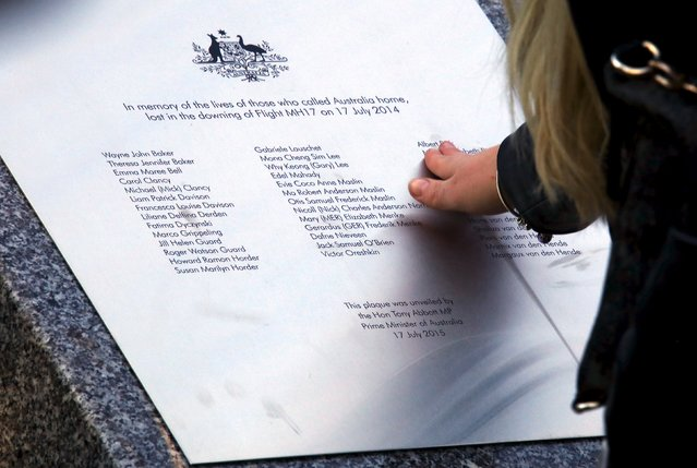 A relative of an Australian victim of Malaysia Airlines jet MH17 touches a memorial that was unveiled outside Parliament House in Canberra, Australia, July 17, 2015. (Photo by David Gray/Reuters)