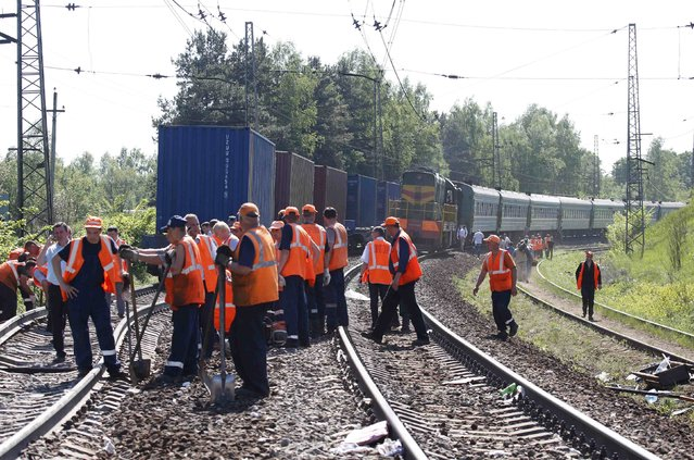 Employees from the repair services and Russian Railways gather near the site of a train collision in Moscow region May 20, 2014. A passenger train on its way to Moldova collided with a freight train near Moscow on Tuesday, killing at least four people and injuring 15, a spokeswoman for Russia's Emergencies Ministry said. The reason for the collision, near the town of Naro-Fominsk 55 km (34 miles) southwest of Moscow, was not immediately clear. (Photo by Grigory Dukor/Reuters)