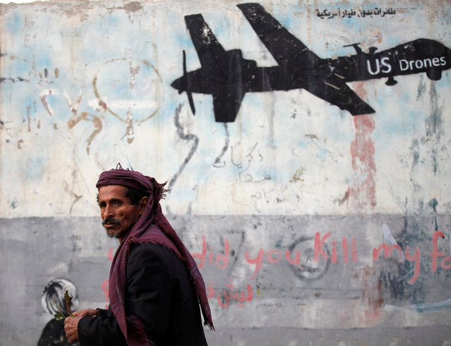 A man walks past a graffiti, denouncing strikes by U.S. drones in Yemen, painted on a wall in Sanaa, Yemen February 6, 2017. (Photo by Khaled Abdullah/Reuters)