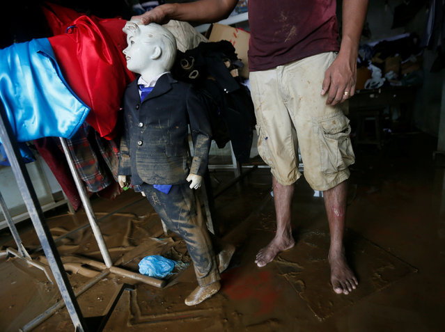 A man holds a muddied mannequin inside his tailoring shop, which was affected by floods, in Biyagama, Sri Lanka May 22, 2016. (Photo by Dinuka Liyanawatte/Reuters)