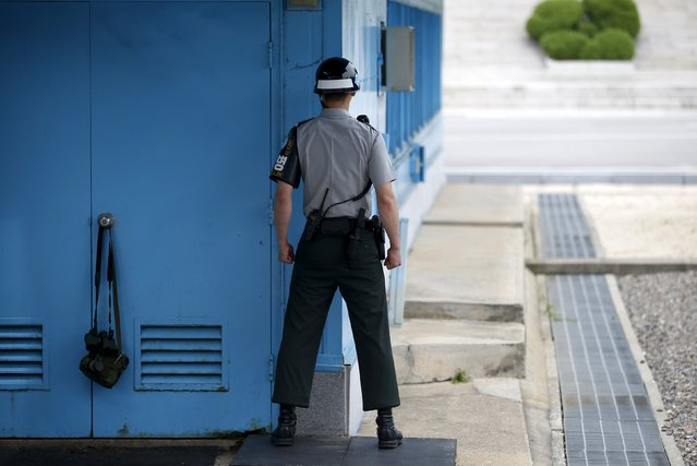 A South Korean soldier stands guard next to a pair of binoculars and belongings hung on the doorknob of the United Nations Command Military Armistice Commission Conference Building at the truce village of Panmunjom, South Korea, July 22, 2015. North Korea has erected a new, taller launch tower at its missile base, possibly in preparation for firing a long-range rocket to mark an important national anniversary in October, South Korea's Yonhap news agency reported on Wednesday. (Photo by Kim Hong-Ji/Reuters)