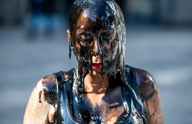 A PETA member, covered in black slime, attends a protest to call attention to the harmful waste associated with the leather industry, outside the Leather, Compliance, & Sustainability Conference on November 13, 2019 in New York City. (Photo by Johannes Eisele/AFP Photo)