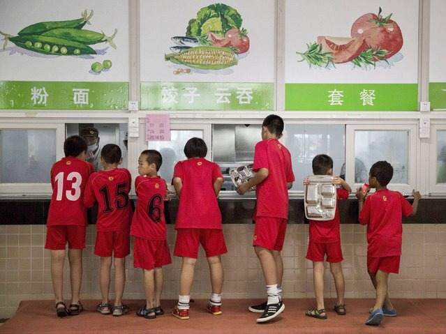 Students wait on line for lunch after training at the Evergrande International Football School near Qingyuan in Guangdong Province. (Photo by Kevin Frayer/Getty Images)