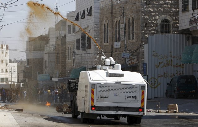 An Israeli truck sprays dirt water at Palestinian stone throwers during clashes in the West Bank city of Hebron July 31, 2015. (Photo by Mussa Qawasma/Reuters)