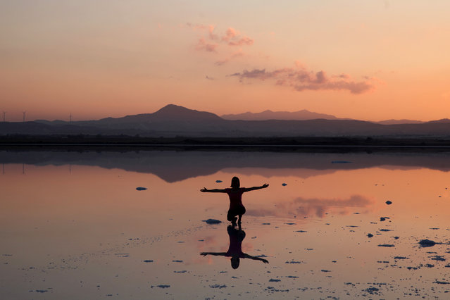 A tourist  poses for a photo during the sunset at a salt lake in Larnaca, Cyprus June 19, 2017. (Photo by Yiannis Kourtoglou/Reuters)