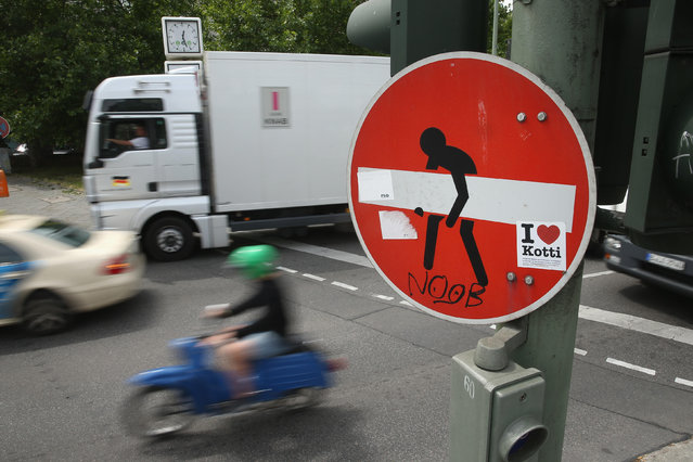 A motorbike passes a traffic sign converted to street art in Kreuzberg district on June 26, 2014 in Berlin, Germany. Berlin, with its long tradition of counter-culture, has become a mecca for street art of all dimensions and messages. (Photo by Sean Gallup/Getty Images)
