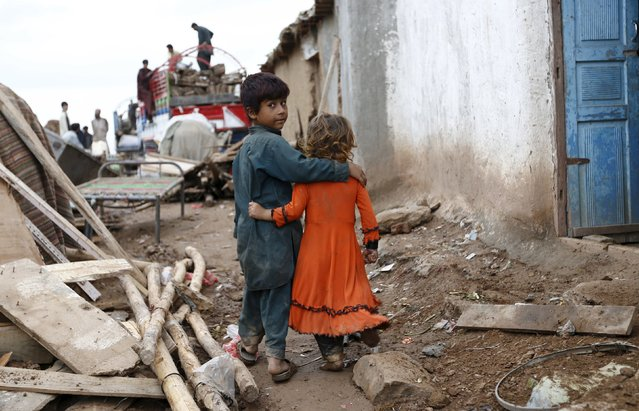 Siblings walk together as people dismantle homes and load belongings onto a truck in a slum in Islamabad, Pakistan August 1, 2015. (Photo by Caren Firouz/Reuters)