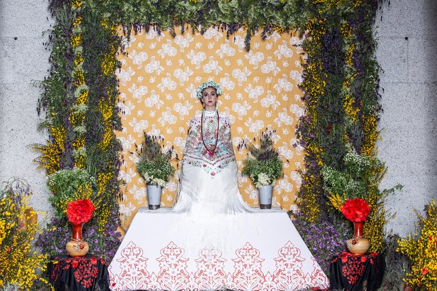 """Leyre Alonso Ramos takes part in the """"Las Mayas"""" festival in Colmenar Viejo near Madrid on May 2, 2019. The Mayas, young girls aged between 7 and 11, are required to sit still in a decorated altar derived from pagan rites celebrating the arrival of spring. (Photo by Benjamin Cremel/AFP Photo)"""