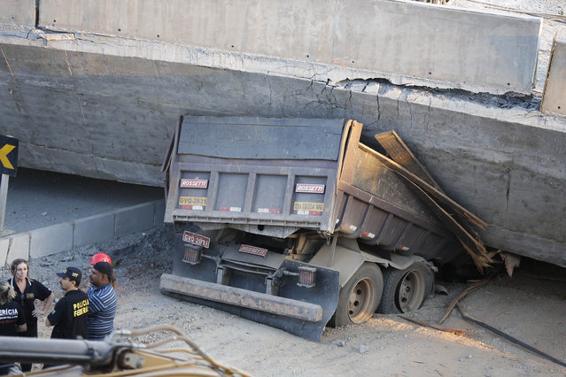 A truck is trapped underneath a collapsed bridge in Belo Horizonte, Brazil, Thursday, July 3, 2014. The overpass under construction collapsed Thursday in the Brazilian World Cup host city. The incident took place on a main avenue, the expansion of which was part of the World Cup infrastructure plan but, like most urban mobility projects related to the Cup, was not finished on time for the event. (Photo by Victor R. Caivano/AP Photo)