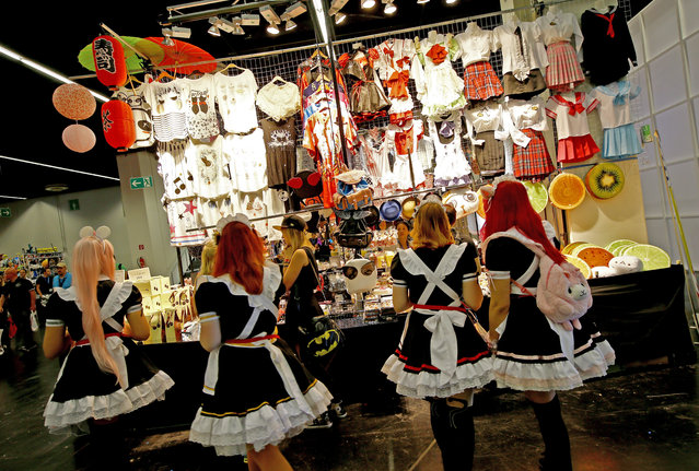 Cosplayers dressed as maids stand in front of a costume shop during the Gamescom 2015 fair in Cologne, Germany August 5, 2015. (Photo by Kai Pfaffenbach/Reuters)
