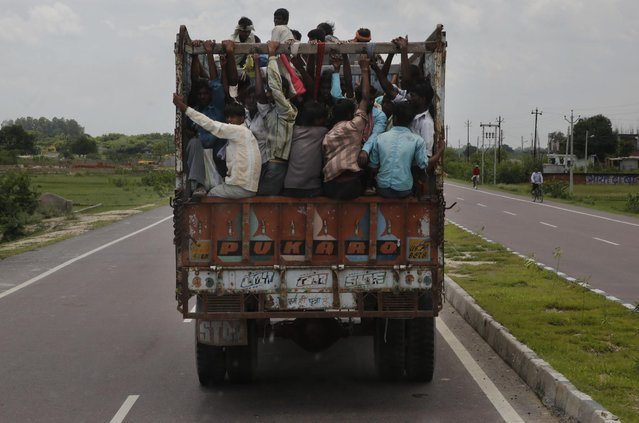 Commuters travel on an overloaded truck on the outskirts of Allahabad, in the northern Indian state of Uttar Pradesh, India, Thursday, July 30, 2015. India's population is set to pass China's in size around 2022, according to the United Nations report released Wednesday, July 29. The current world population is 7.3 billion with China and India each having more than one billion people. (Photo by Rajesh Kumar Singh/AP Photo)