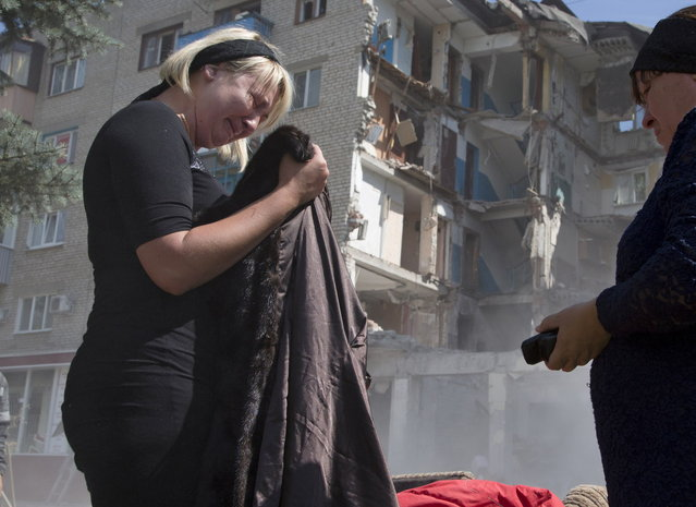 Eugenia Gubareva, left, cries after finding clothes belonging to her parents, who were killed in a building destroyed by shelling in Mikolaivka village, near the city of Slovyansk, Donetsk Region, eastern Ukraine Thursday, July 10, 2014. In the past two weeks, Ukrainian government troops have halved the amount of territory held by the rebels. Now they are vowing a blockade of Donetsk. (Photo by Dmitry Lovetsky/AP Photo)