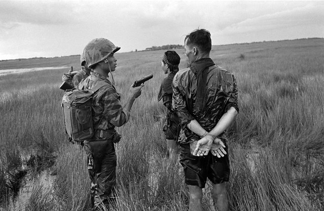 A South Vietnamese soldier holds a cocked pistol as he questions two suspected Viet Cong guerrillas captured in a weed-filled marsh in the southern delta region late in August 1962