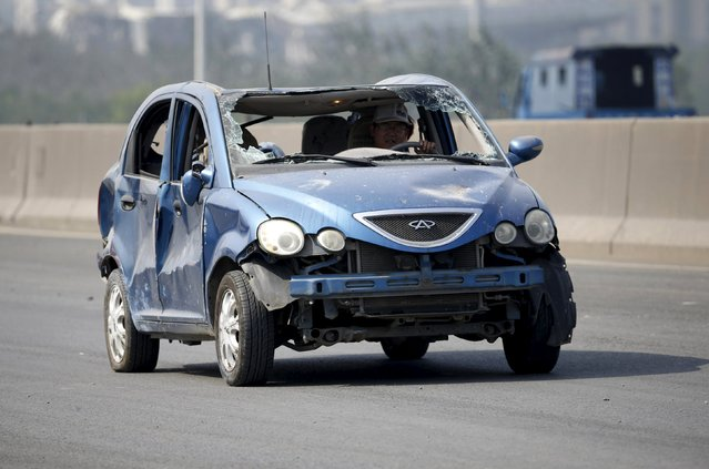 A driver is seen inside a damaged car on a highway near the site of the explosions at the Binhai new district in Tianjin August 13, 2015. Two massive explosions caused by flammable goods ripped through an industrial area in the northeast Chinese port city of Tianjin late on Wednesday, killing 17 people and injuring around 400, official Chinese media reported. (Photo by Jason Lee/Reuters)