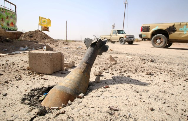 An unexploded mortar shell is seen half buried in the ground in Fallujah, 50 kilometres (30 miles) from the Iraqi capital Baghdad, after Iraqi forces retook the embattled city from the Islamic State group on June 26, 2016. Iraqi Prime Minister Haider al-Abadi urged all Iraqis to celebrate the recapture of Fallujah by the security forces and vowed the national flag would be raised in Mosul soon. While the battle has been won, Iraq still faces a major humanitarian crisis in its aftermath, with tens of thousands of people who fled the fighting desperately in need of assistance in the searing summer heat. (Photo by Haidar Mohammed Ali/AFP Photo)
