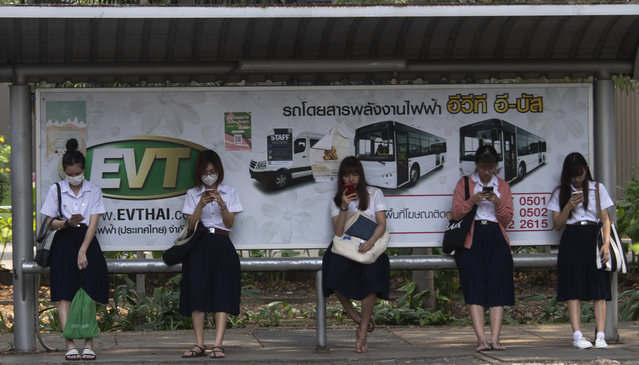 Students from Chulalongkorn University wear face masks to protect themselves from poor air quality as they wait at a bus stop in Bangkok, Thailand, Monday, January 20, 2020. (Photo by Sakchai Lalit/AP Photo)