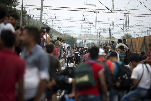 Migrants wait for a train to arrive, at Gevgelija train station in Macedonia, close to the border with Greece, August 14, 2015. (Photo by Stoyan Nenov/Reuters)