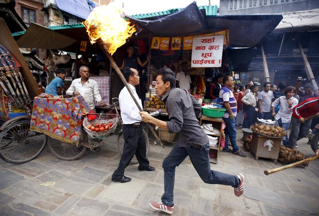 A protester holding a torch runs past police (not pictured) trying to stop the protesters from marching in a rally organised by a 30-party alliance led by a hardline faction of former Maoist rebels, who are protesting against the draft of the new constitution, in Kathmandu August 15, 2015. (Photo by Navesh Chitrakar/Reuters)