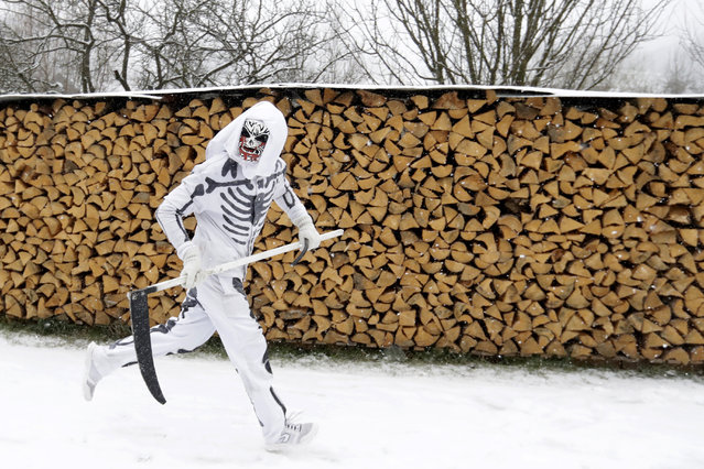 A reveler depicting a grim reaper runs during a traditional St Nicholas procession in the village of Valasska Polanka, Czech Republic, Saturday, December 7, 2019. This pre-Christmas tradition has survived for centuries in a few villages in the eastern part of the country. The whole group parades through village for the weekend, going from door to door. St.Nicholas presents the kids with sweets. The devils wearing home made masks of sheep skin and the white creatures representing death with scythes frighten them. (Photo by Petr David Josek/AP Photo)