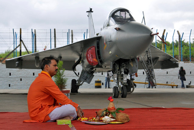 A Hindu priest waits to perform prayers next to Tejas, India's first locally-built Light Combat Aircraft (LCA), before its induction into the Indian Air Force at the Hindustan Aeronautics Limited (HAL) Airport in Bengaluru, India, July 1, 2016. (Photo by Abhishek N. Chinnappa/Reuters)