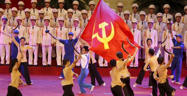 A man waves a communist flag during celebrations to commemorate the 70th anniversary of the establishment of the Vietnam Public Security police force at the National Convention Center in Hanoi August 18, 2015. (Photo by Reuters/Kham)