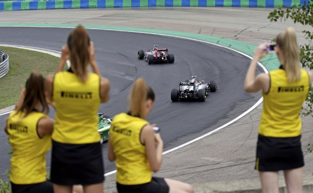 Pirelli hostesses take pictures as drivers compete during the Hungarian F1 Grand Prix at the Hungaroring circuit, near Budapest July 27, 2014. (Photo by David W. Cerny/Reuters)