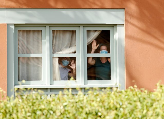 Guests, wearing protective face mask, look through a window at H10 Costa Adeje Palace, which is on lockdown after cases of coronavirus have been detected there in Adeje, on the Spanish island of Tenerife, Spain, February 26, 2020. (Photo by Borja Suarez/Reuters)