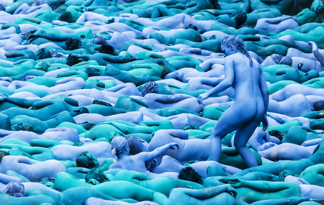 People manoeuvre into position as they take part in a mass nude art installation entitled Sea of Hull by New York based artist Spencer Tunick in Hull, England, Saturday July 9, 2016. (Photo by Danny Lawson/PA Wire via AP Photo)