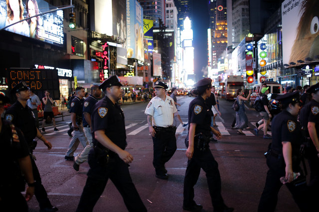 NYPD officers keep an eye on protesters as they go through Times Square taking part in a protest against the killing of Alton Sterling, Philando Castile and in support of Black Lives Matter during a march along Manhattan's streets in New York July 8, 2016. (Photo by Eduardo Munoz/Reuters)