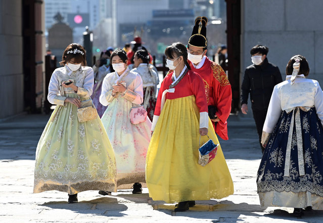 People in traditional Korean hanbok dresses wear face masks as they visit Gyeongbokgung palace in Seoul on February 23, 2020. South Korea reported two additional deaths from coronavirus and 123 more cases on February 23, with nearly two thirds of the new patients connected to a religious sect. The national toll of 556 cases is now the second-highest outside of China. (Photo by Jung Yeon-je/AFP Photo)
