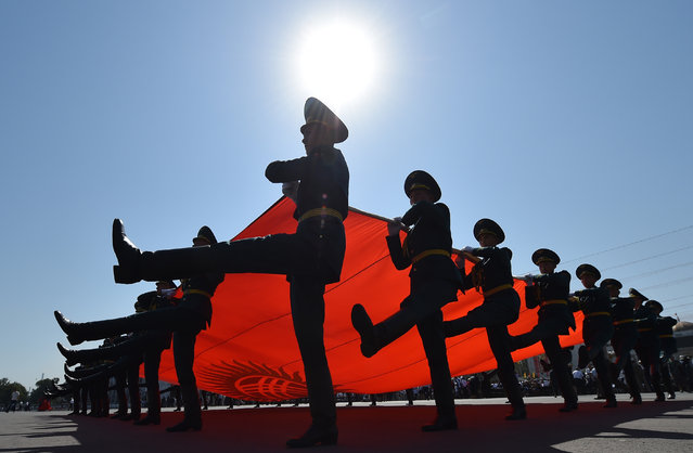 Kyrgyz honour guards carry their national flag as they parade during celebrations marking the 26th anniversary of Kyrgyzstan's independence from the Soviet Union at the Ala-Too Square in Bishkek on August 31, 2017. (Photo by Vyacheslav Oseledko/AFP Photo)