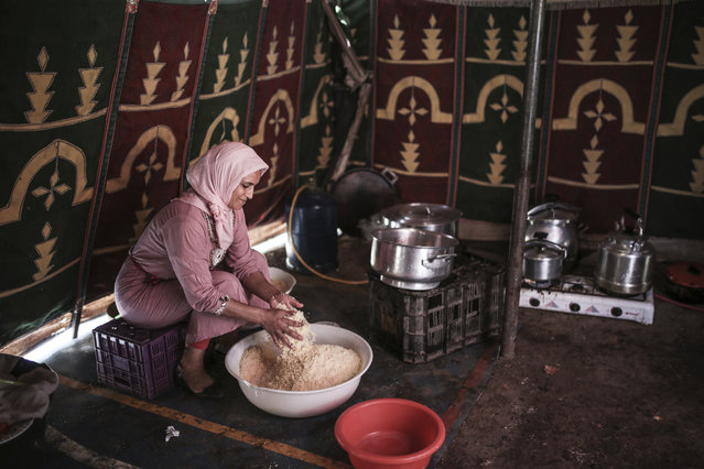 In this Thursday, August 17, 2017 photo, a woman cooks couscous for horsemen taking part in Tabourida, a traditional horse riding show also known as Fantasia, in Mansouria, near Casablanca, Morocco. (Photo by Mosa'ab Elshamy/AP Photo)
